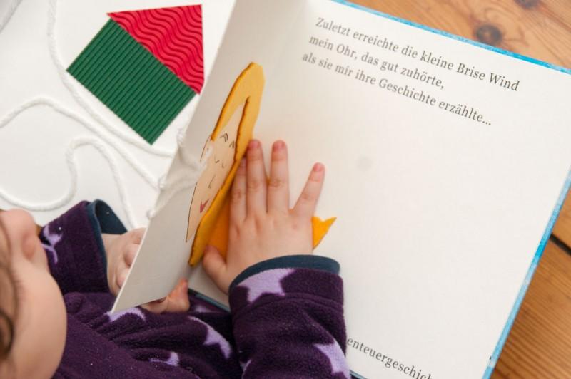 Das Buch Die kleine Brise Wind erzählt eine lyrische Geschichte in taktilen Illustrationen, Großschrift und Braille Punktschrift