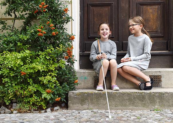 Zwei Mädchen sitzen vor einer Tür