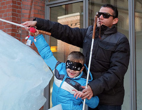 Der blinde Mobilitätstrainer Juan Ruiz trainiert mit einem Kind Klicksonar, sie haben durch Klicken und den Einsatz ihrer Langstöcke eine Eisskulptur entdeckt